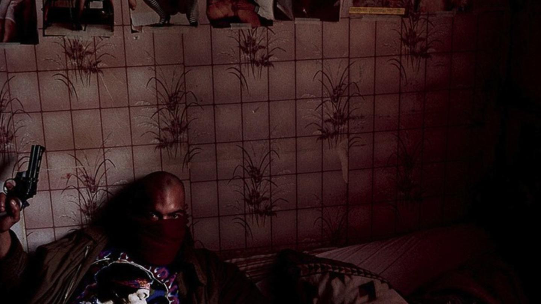 """Guy Georges posa com uma arma de fogo em um quarto onde, provavelmente, o CNT fazia suas reuniões. Nota-se na parede, acima dele, fotos de mulheres nuas. """"Eu gostava de cruzar a famosa prisão revolucionária, a Bastilha."""" Data da imagem desconhecida."""
