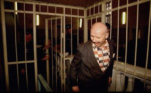 Na Foto: Andrei Chikatilo dá um sorriso estranho ao caminhar por sua jaula.