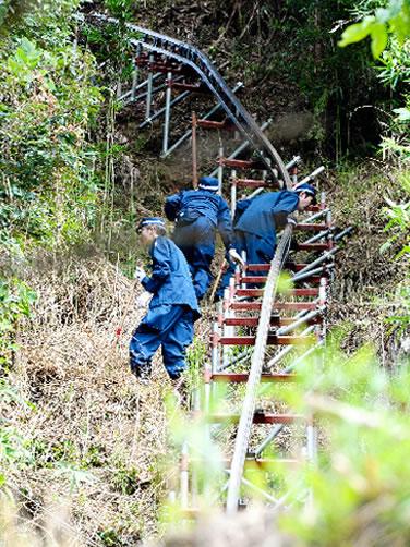 Na foto: Policiais fazem busca no entorno da aldeia de Mitake. Créditos: Asahi.