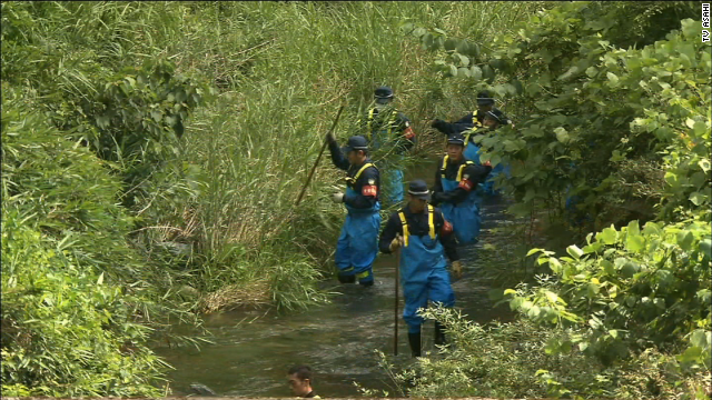 Na foto: Policiais japoneses fazem buscas em riacho na aldeia de  Créditos: CNN.