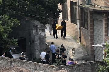 Na foto: Policiais carregam corpo de uma das vítimas. Créditos: Japan Times.