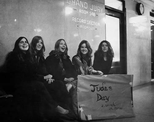"""Mulheres membros da família Manson do lado de fora da sala de júri. No cartaz a frase: """"Dia do Judas""""."""