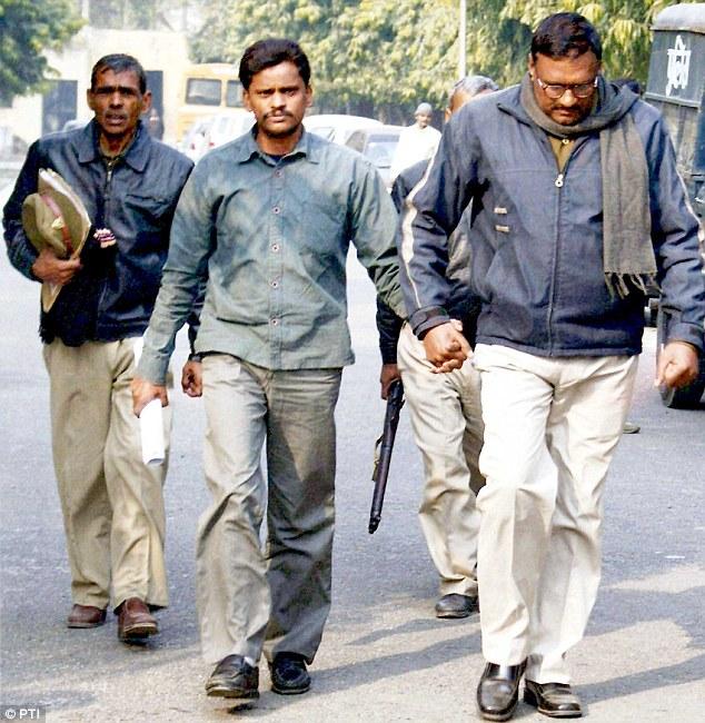 Polícia leva Surinder Koli, acusado de sequestro, estupro e assassinato de crianças em Nithari, para a prisão após audiência em Ghaziabad, 2010. Créditos: AP PHoto.