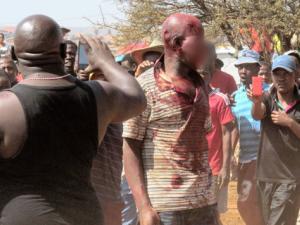 Na foto: Moradores tiram fotos e filmam agressão a o suposto serial killer. Créditos: Pretoria News.
