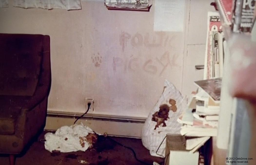 """Na foto: O símbolo dos Panteras Negras, uma pata, e as palavras """"Political Piggy"""" na parede da casa de Gary Hinman. Beausoleil esfaqueou Hinman várias vezes, e enquanto ele estava morrendo, Beausoleil mergulhou sua mão em seu sangue e imprimiu uma pegada na parede. Em seguida, usando o dedo de uma luva mergulhada na piscina sangrenta, Beausoleil escreveu """"PORCO POLÍTICO"""" na parede perto da pegada de sangue.Créditos: Cielodrive.com."""