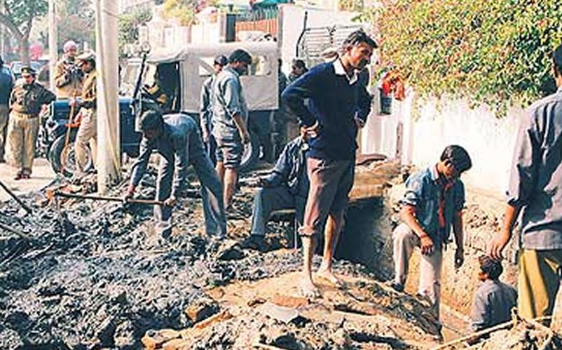 Na foto: Trabalhadores e polícia recolhem pedaços de corpos de um esgoto em Noida, periferia de Nova Délhi, onde o serial killer Surinder Koli descartava suas vítimas. Foto AFP.