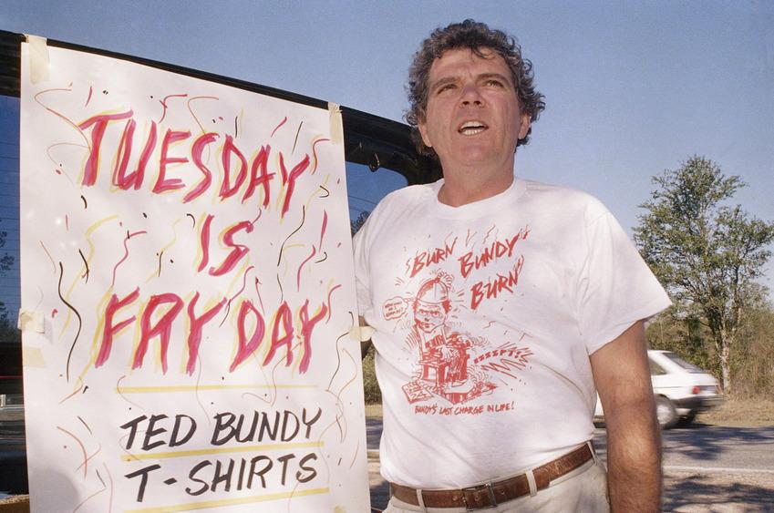 """Na foto: Um dia antes da execução de Ted Bundy, homem vende camisetas com a inscrição """"Frite Bundy Frite"""" nos arredores da Prisão Estadual da Flórida. Créditos: Spiegel."""