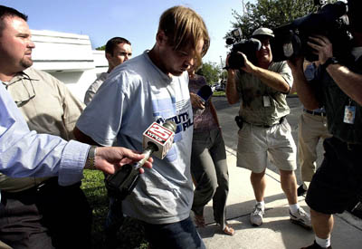 O serial killer Eugene McWatters é levado para delegacia após ser preso. Foto: Reprodução Internet.