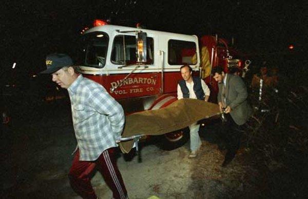 Em 25 de Março de 1987, homens removem o corpo de Deborah Dudley de uma área florestal perto de Hammonton, Nova Jérsei. Foto: AP Photo/Charles Krupa.