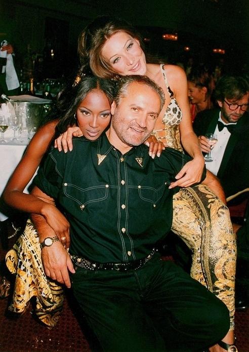 O estilista italiano Gianni Versace ao lado das beldades Naomi Campbell e Carla Bruni. Getty Images.