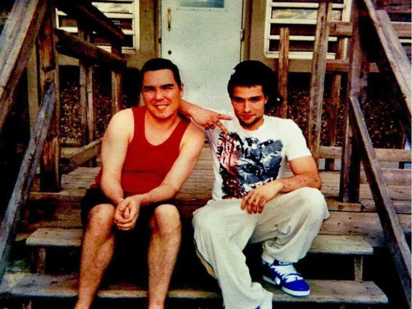 Luka Magnotta, sorrindo ao lado de seu amigo pedófilo Jonathan Lafrance-Rivard na escadaria de madeira da prisão de Archambault, em Quebec.