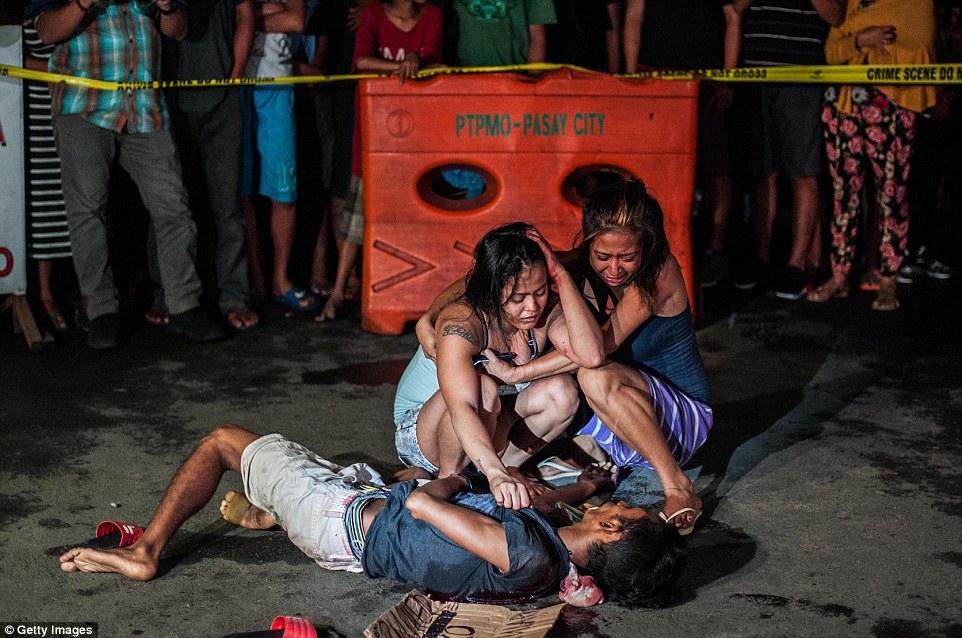 Mulheres choram sob o corpo de um familiar morto por motociclistas em Manila, no dia 23 de julho de 2016. Foto: Getty Images.