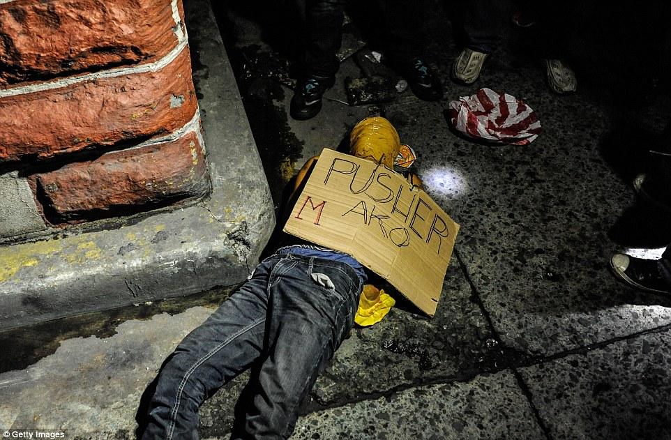 """Suposto traficante morto em Manila. Seu rosto foi coberto com fita adesiva e um cartaz escrito """"Traficante"""" deixado em cima do corpo. Foto: Getty Images."""