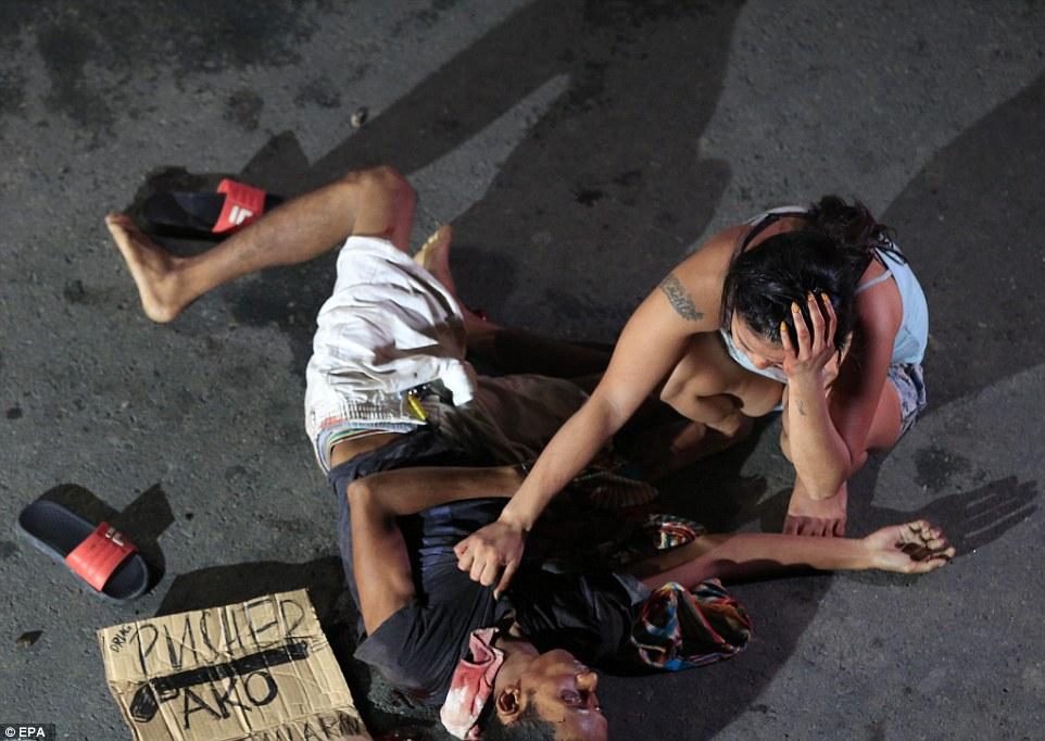 """Cartaz escrito """"Traficante"""" foi deixado ao lado do corpo. Foto: Getty Images."""