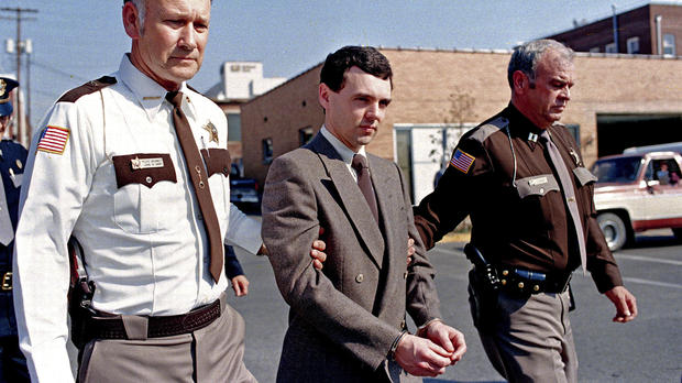 Novembro de 1987: o serial killer Donald Harvey é levado até a delegacia do Condado de Laurel, Kentucky, após se declarar culpado de mais oito mortes no tribunal. Do lado esquerdo o Xerife Floyd Brummett. (AP Photo/Ed Reinke)