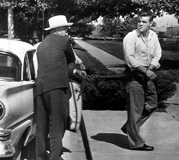 Charles Starkweather, 19 anos, assassino de 11 pessoas, é levado acorrentado por um delegado após ser condenado a sentar na cadeira elétrica. Data: 24 de maio de 1958, Licoln, Nebraska. (AP Photo/Str)