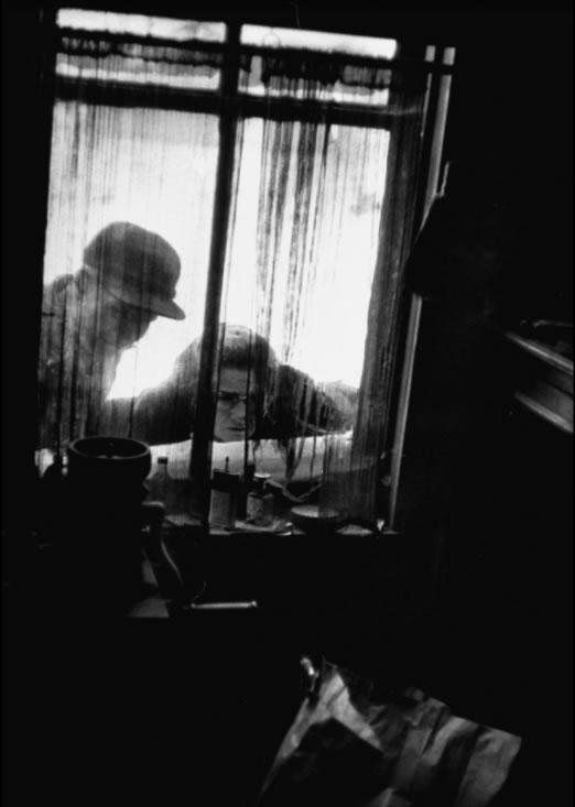 OLHANDO PARA O MUNDO DE GEIN, um homem e uma mulher atravessam seus olhares pela cortina suja e esfarrapada e vêem a cozinha toda em desordem. Todos de Plainfield foram ver a casa que eles antes ignoravam. Foto: Life - 2/12/1957.