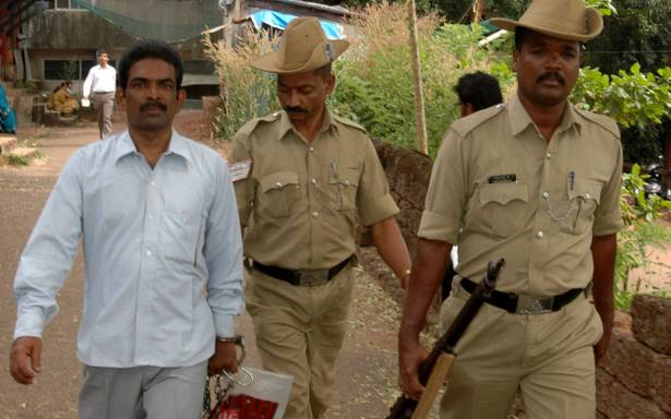 """O serial killer """"Mohan Cianeto"""" caminha ao lado de policiais. Foto: Times of India."""