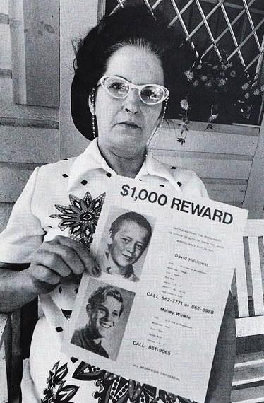 A mãe de David Hilligiest segura um cartaz com uma recompensa de mil dólares por informações de David e seu amigo Gregory.