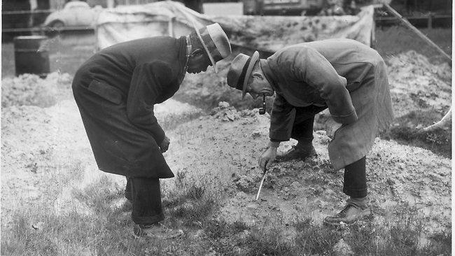 O detetive de polícia Haygarth e um rastreador aborígene examinam pegadas no local onde o corpo de Gladys Hosking foi encontrado em Royal Park. Foto: HWT Library.