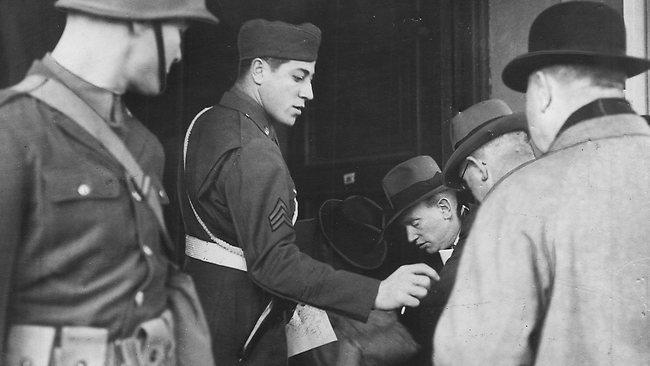 Soldados americanos checam as credenciais dos detetives que se apresentaram na corte marcial de Edward Leonski.