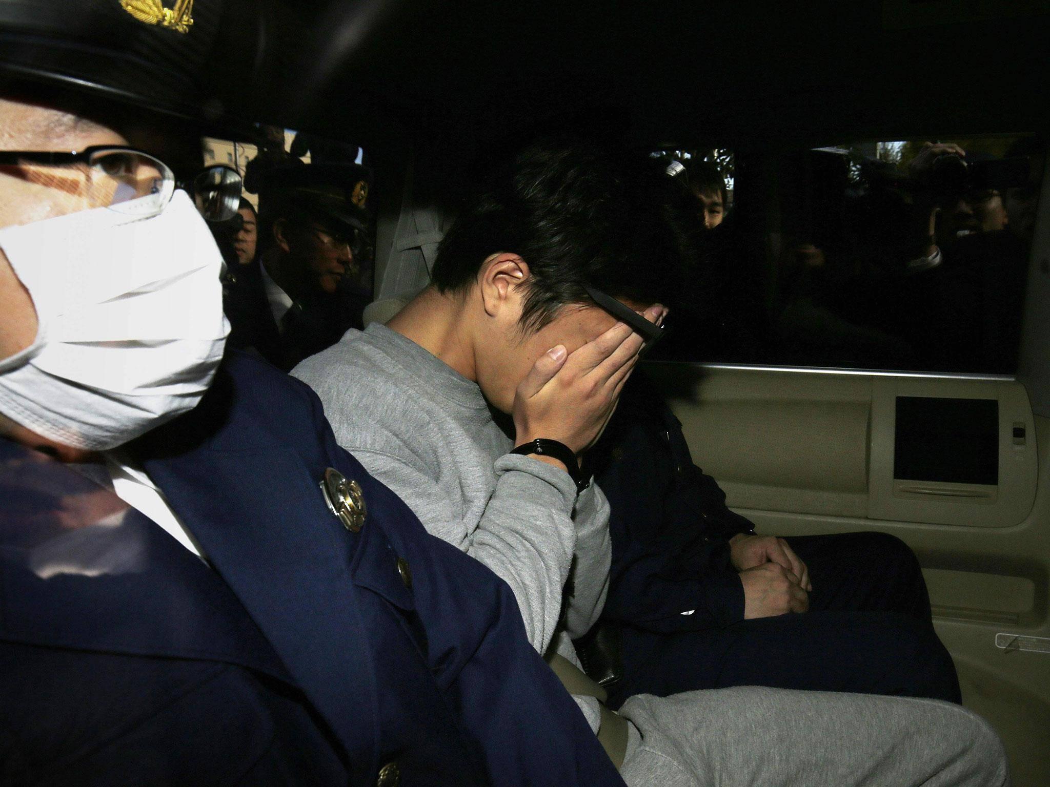 Takahiro Shiraishi esconde o rosto ao ser levado até o escritório do promotor público de Tóquio. Foto: Getty Images.