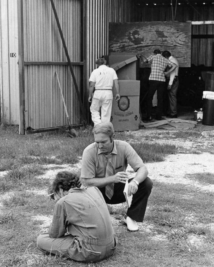 Wayne Henley, sentado e com as mãos na cabeça, é questionado pelo detetive Karl Siebeneicher em frente a garagem de barcos. Foto: David Nance, Houston Chronicle.