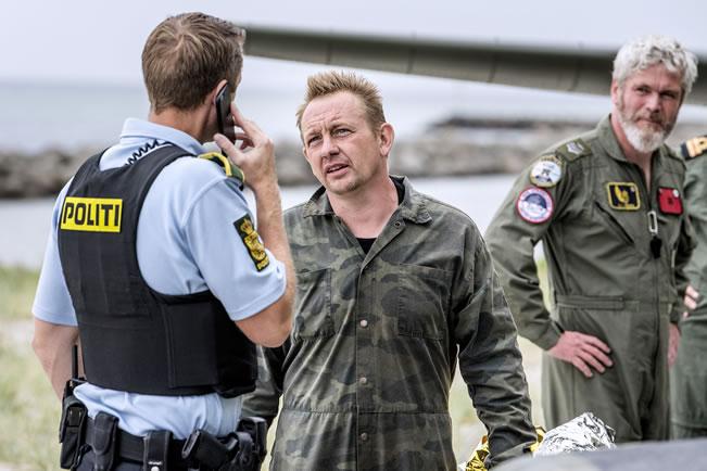 O empresário Peter Madsen (ao centro) durante custódia policial após ser resgatado em alto-mar.