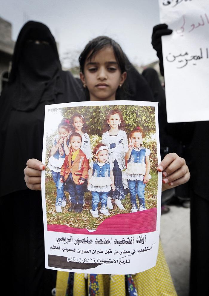 Uma criança iemenita carrega o cartar de uma família inteira morta no ataque aéreo do dia 26 de Agosto. Foto: Mohammed Huwais/Agence France-Presse -- Getty Images.