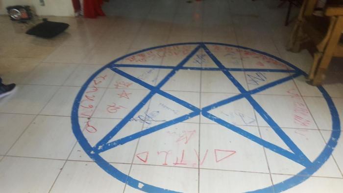 No chão do templo há um pentagrama desenhado com escritos em vermelho, possivelmente sangue. Foto: Polícia Civil RS.