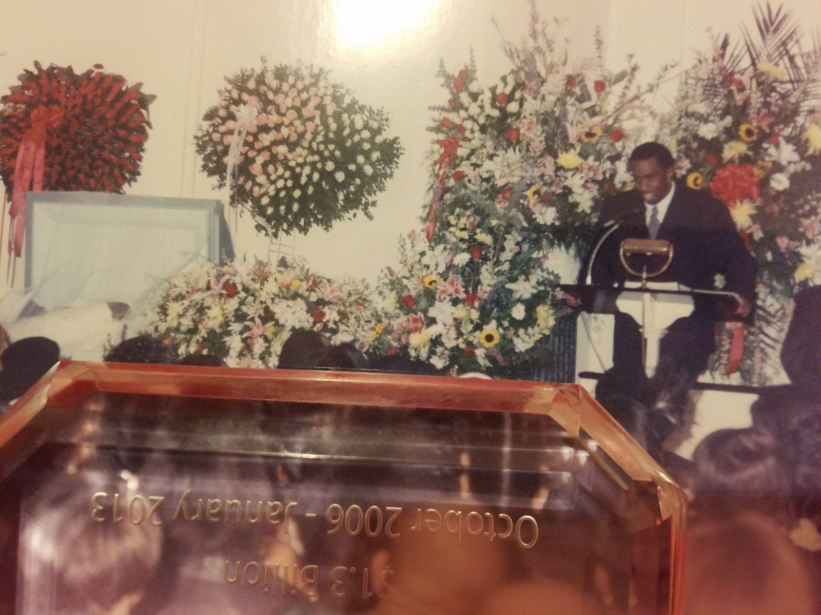 Puffy Combs discursa no velório de Notorious B.I.G. À esquerda na foto é possível ver a tampa do caixão aberta. Notorious foi enterrado vestido de branco e em um caixão branco. Foto: The Coli Forum.