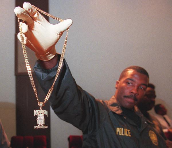 Policial do LAPD segura um medalhão de ouro com o símbolo da Death Row. Membros da gravadora usavam esse medalhão com forma de status.
