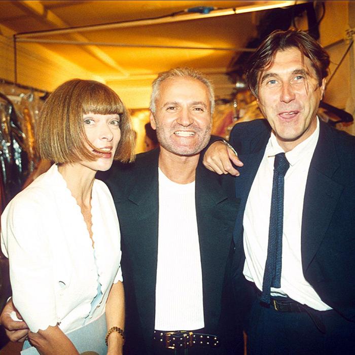 A editora-chefe da revista Vogue, Gianni Versace e o cantor britânico Bryan Ferry (fundador da excelente banda de rock Roxy Music, mas mais conhecido por seu hit internacional Slave to Love) em um desfile do estilista em 1994. Foto: Richard Young/Rex/Shutterstoc.