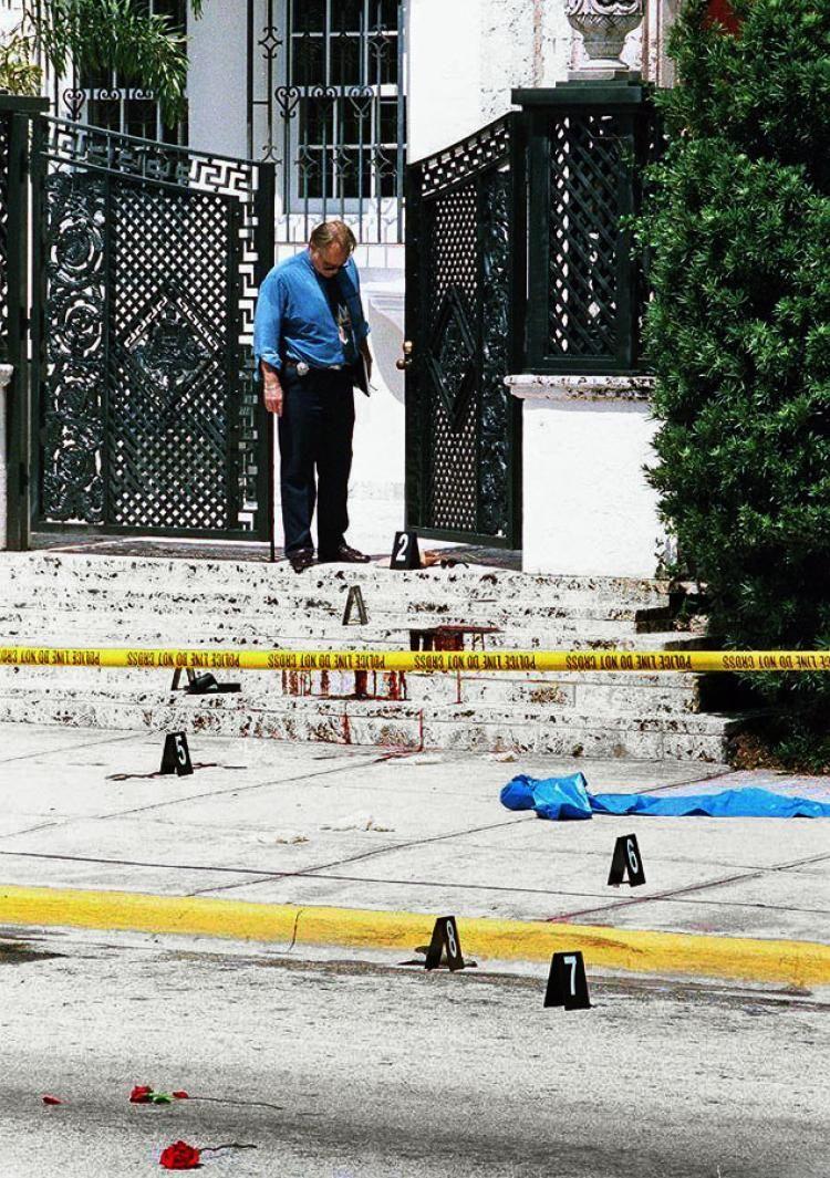 Investigador de polícia olha para as manchas de sangue na escadaria da mansão do estilista Gianni Versace. É possível ver a sandália de Versace, no segundo degrau. Foto: Robert Sullivan/AFP/Getty Images.
